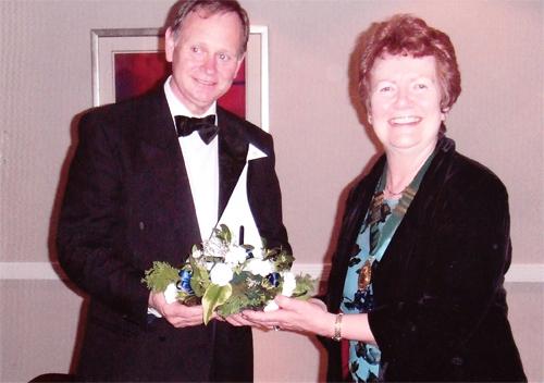 Nat. Chairman Margaret Gray handing over floral arrangement to Mr Mark Longford at formal dinner.